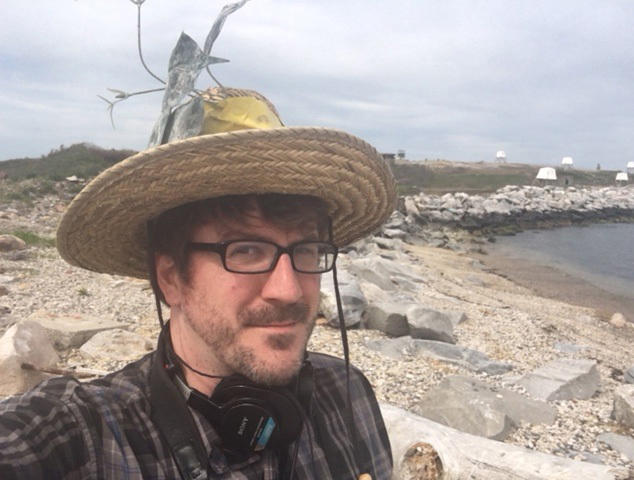 A straw hat with a camouflage flower ensures safety from the dive bombing terns of Great Gull Island.