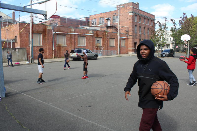 Students playing basketball in a gym class at New Light High School.