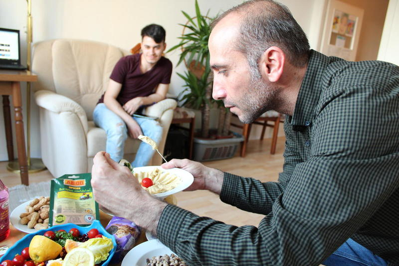 At his studio apartment in Dresden, Bassel prepares a plate of homemade hummus to enjoy at sunset during Ramadan, the holiest month in Islam, which is observed with fasting and prayer.