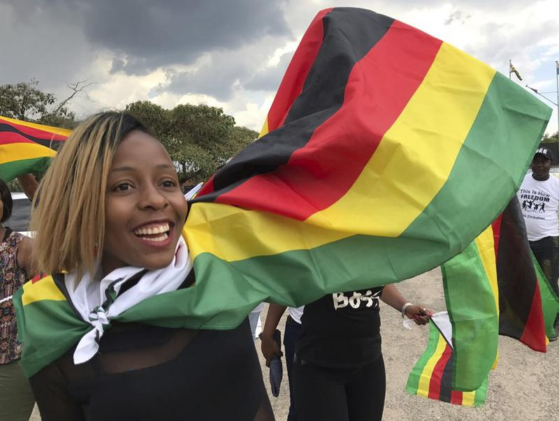 A supporter waits for recently fired Zimbabwe Vice President Emmerson Mnangagwa at the Manyame Air Force Base in Harare on Wednesday. Mnangagwa is to be sworn in as the country's new leader after Robert Mugabe announced his resignation Tuesday.