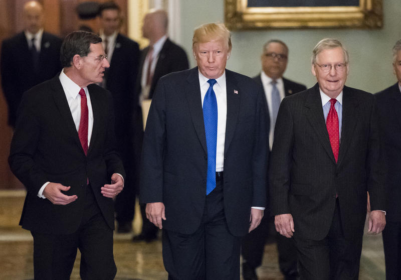 President Trump, escorted by Sen. John Barrasso, R-Wyo., chairman of the Senate Republican Policy Committee, left, and Senate Majority Leader Mitch McConnell, R-Ky., right, arrives at the Capitol to meet with GOP lawmakers about passing the GOP tax bill.