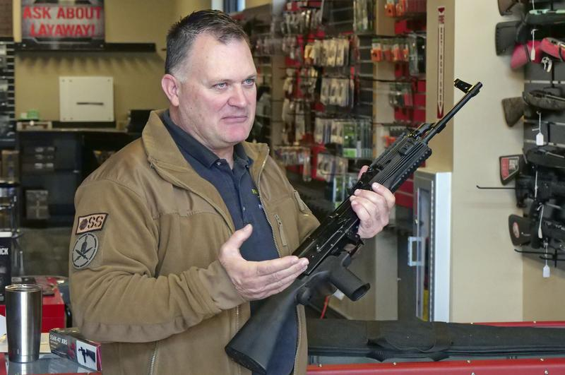 """Clark Aposhian, chairman of the Utah Shooting Sports Council, demonstrates how a little-known device called a """"bump stock"""" works when attached to a semi-automatic rifle at the Gun Vault store and shooting range in South Jordan, Ut."""