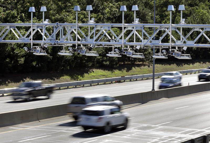 Cars pass under toll sensor gantries hanging over the Massachusetts Turnpike in Newton, Mass., in 2016.