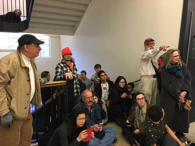 Students, faculty and others watch as the sun creeps down MIT's Infinite Corridor. MIThenge discoverer Tom Norton is pictured top-left, watching, while lying flat on the landing.