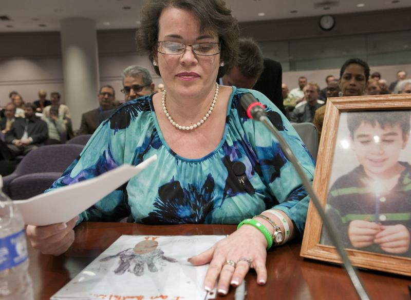 Veronique Pozner places her hand next to artwork made by her son Noah before a 2013 legislative subcommittee reviewing gun laws in Hartford. Noah Pozner was among those killed in the 2012 mass shooting at Sandy Hook Elementary School in Newtown.