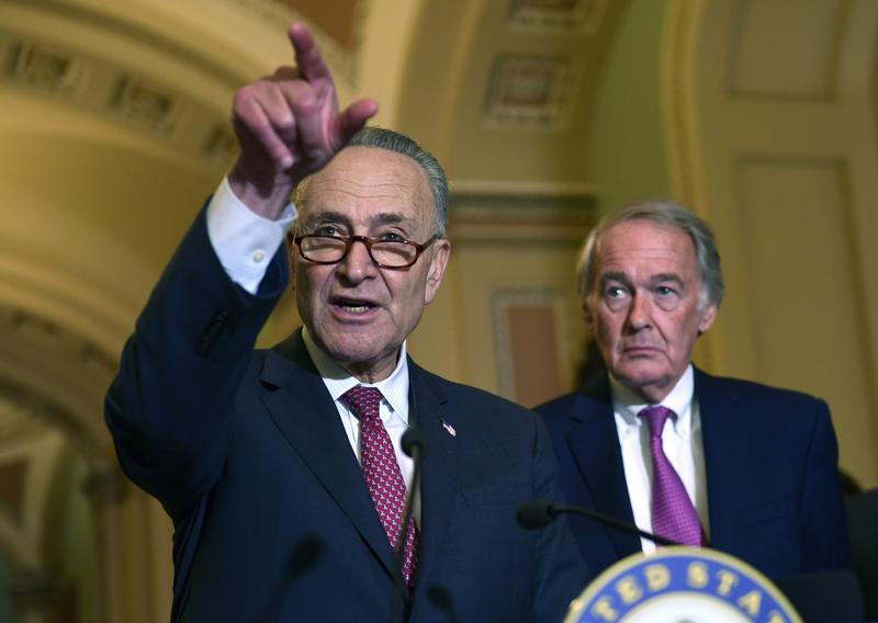 Senate Minority Leader Sen. Chuck Schumer of N.Y., left, standing with Sen. Edward Markey, D-Mass., right, speaks to reporters on Capitol Hill in October.
