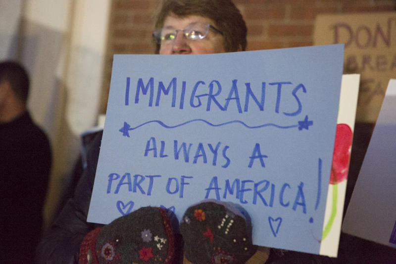 A woman holds a sign outside City Hall at a community gathering held in support of Cumbicos that evening.