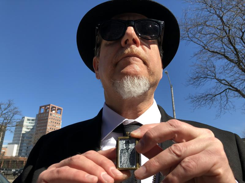 Researcher Michael Bielawa shows off his locket – featuring artwork by UFOlogist Albert K. Bender – and his stylish Men in Black outfit.