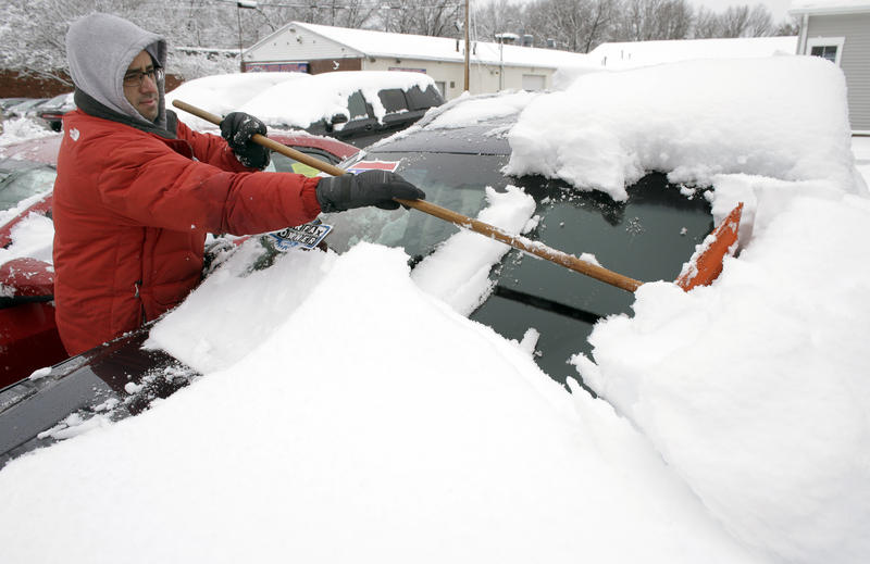 Bruno Medina, of Natick, Mass., removes snow from vehicles at a used car lot last week.