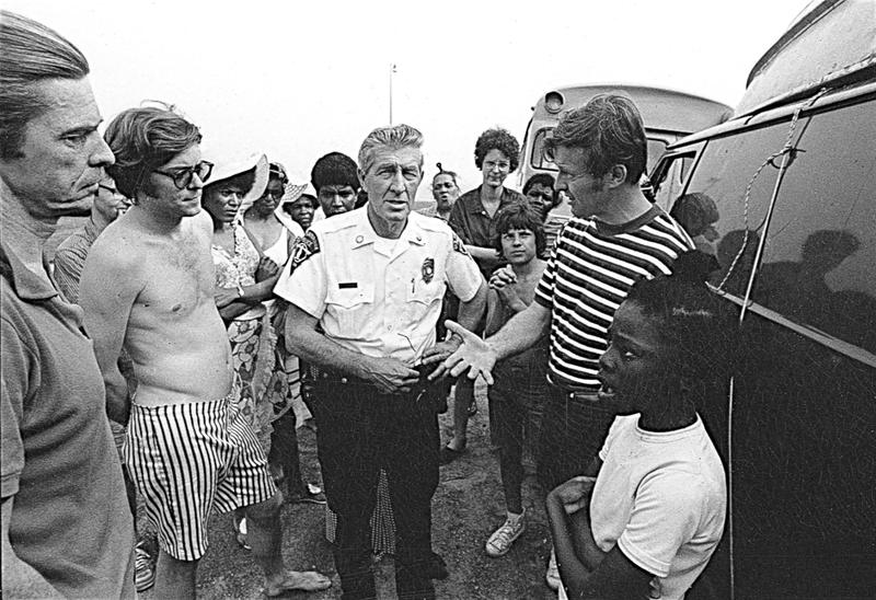 Activist Ned Coll, in striped shirt, talks with a police officer and community members as part of his campaign to enable African-Americans and the urban poor to access Connecticut's beaches in the 1960s and '70s.