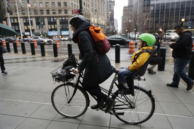 A woman commutes by bicycle with her son riding in back in New York in January.