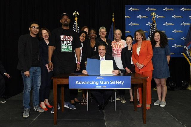 Governor Cuomo takes a photo with gun control advocates, including U.S. House Minority Leader Nancy Pelosi, as he signs legislation to remove guns from domestic abusers and require them to surrender all firearms.