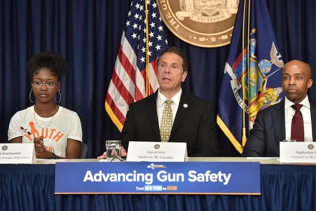 Governor Cuomo sits between Aalayah Eastmond, who survived the mass shooting at Marjory Stoneman Douglas High School in February, and Alphonso David, counsel to the governor, as he announces the extreme risk protection order to help prevent gun violence.