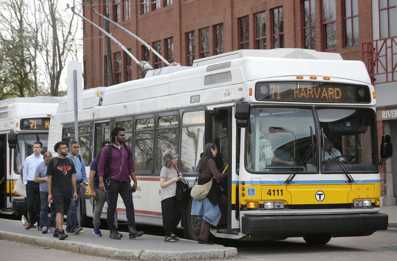 Passengers board a bus powered by electricity supplied through overhead wires, in Watertown, Mass., in May.