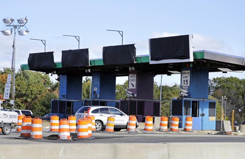 A car travels through a partially dismantled toll booth on the Massachusetts Turnpike in 2016. Boston migrated to all-electronic tolling on the Mass Pike that same year.