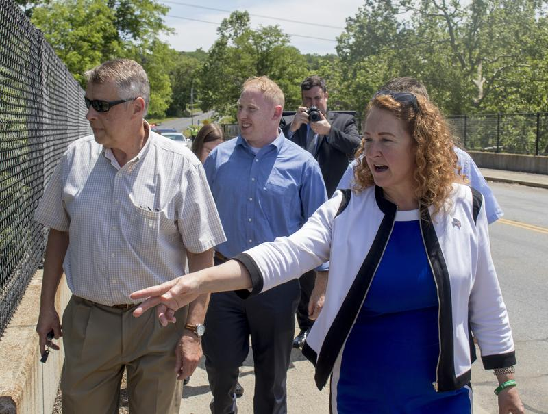 U.S. Representative Elizabeth Esty and FEMA officials walk across a Route 7 overpass, stopping to look at a greenway that has been off limits to residents since the storm.