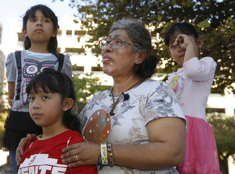 Lucia Ajas, middle, talks about her and her children, Regina Vargas, 7, left, Akemi Vargas, 8, second from left, and Trinidad Vargas, 5, right, being separated from their father during an immigration family separation protest in Phoenix on Monday.