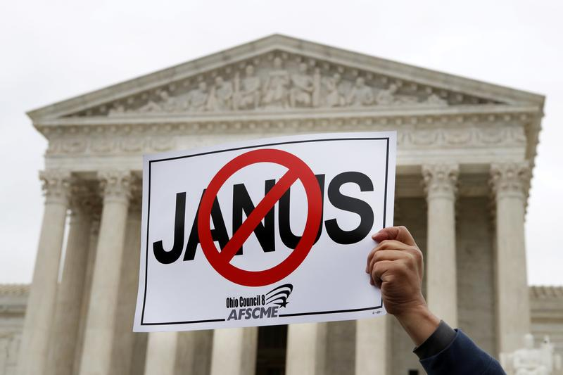 Stephen Roberts, with the American Federation of State, County and Municipal Employees (AFSCME), holds up a sign against Mark Janus during a rally outside of the Supreme Court in Washington in February.