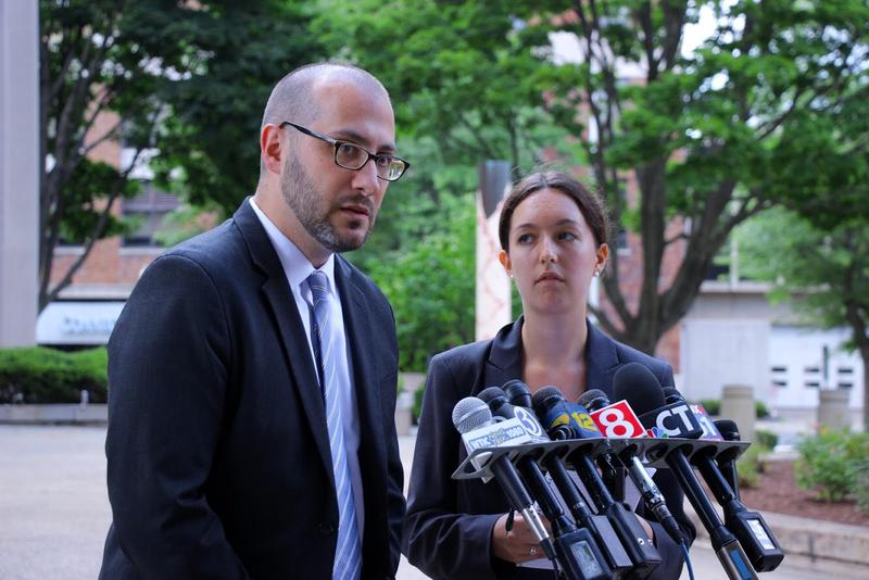 Joshua Perry, deputy director of Connecticut Legal Services, and Carolyn O'Connor with the Yale Immigration Legal Services clinic speak to reporters on the steps of the federal courthosue in Bridgeport on Wednesday.