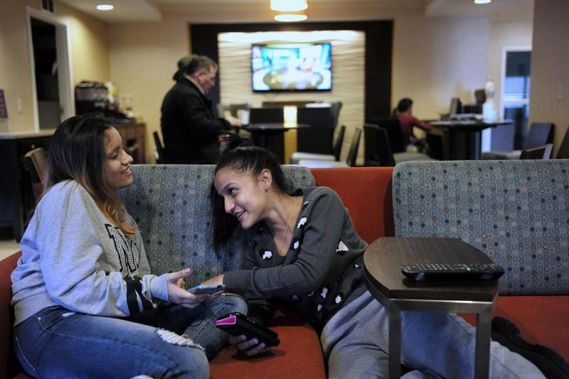 15-year-old Alanis Rodriguez, of Canovanos, Puerto Rico, left, and 14-year-old Bethel Sanchez, of Isabela, Puerto Rico, spend time together in a hotel lobby in Dedham, Mass.