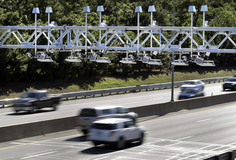 FILE - In this Aug. 22, 2016 file photo, cars pass under toll sensor gantries hanging over the Massachusetts Turnpike in Newton, Mass.