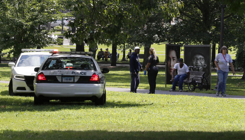 A police officer speaks to a man walking on New Haven Green, Wednesday in New Haven, Conn.