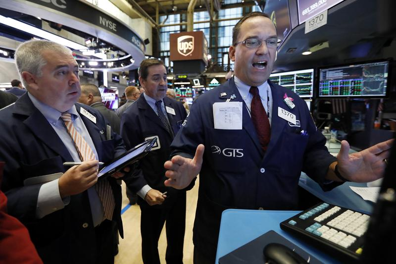 Trader Edward McCarthy, left, and specialist Anthony Matesic, right, work on the floor of the New York Stock Exchange Friday.