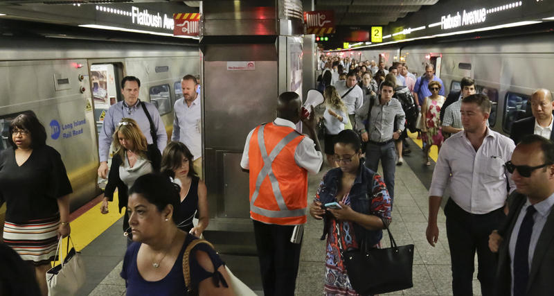 An MTA employee, center, uses a bullhorn to direct LIRR commuters to subway options at Atlantic Terminal in Brooklyn N.Y., as Amtrak begins emergency repair work at Penn Station in 2017.