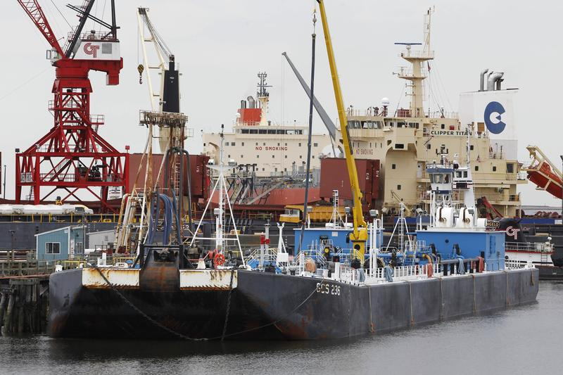 A barge, front, is seen docked in front of cargo vessels at the Port of New Haven, in New Haven, Conn.