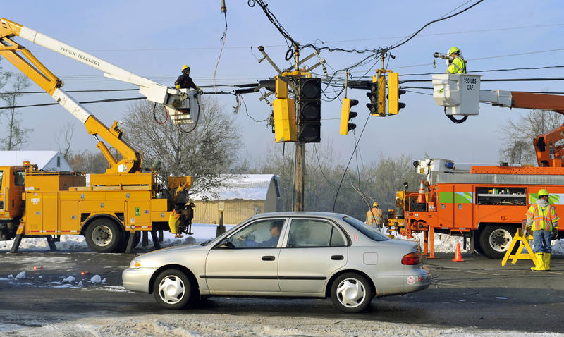 A vehicle passes under a traffic light damaged by a storm as department of transportation and power workers repair downed lines on Route 5 in South Windsor, Conn.
