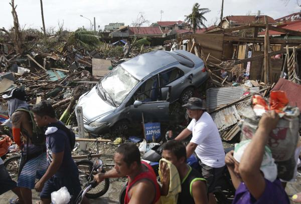 Survivors move past the damages caused by Typhoon Haiyan in Tacloban city, Leyte province central Philippines on Monday, Nov. 11, 2013. Authorities said at least 2 million people in 41 provinces had been affected by Friday's disaster and at least 23,000 houses had been damaged or destroyed.