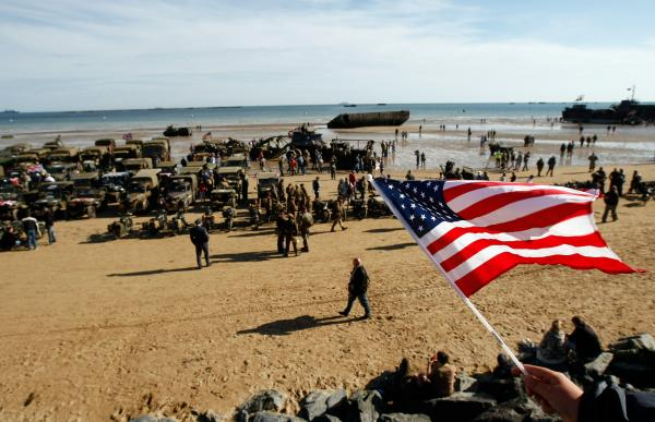 An onlooker waves an American flag as World War II military vehicles are displayed on the beach of Arromanches, France, Friday, June 6, 2014, as part of D-Day commemorations. World leaders and veterans gathered by the beaches of Normandy, northern France, on Friday to mark the 70th anniversary of the World War II D-Day landings.