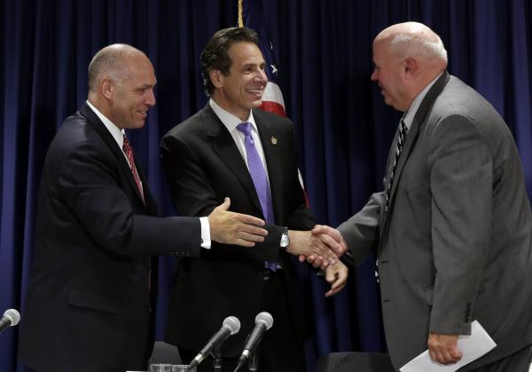 Anthony Simon, general chairman of the United Transportation Union, left, Metropolitan Transportation Authority Chairman Thomas Prendergast, right, and New York Gov. Andrew Cuomo share a collective hand shake after a tentative labor agreement for the Long Island Rail Road was reached.