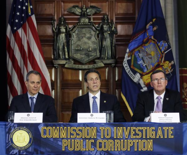 New York Gov. Andrew Cuomo, center, speaks during a news conference as New York Attorney General Eric Schneiderman, left, and Onondaga County District Attorney William Fitzpatrick listen on Tuesday, July 2, 2013, in Albany, N.Y.