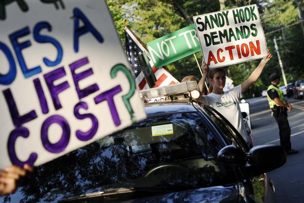 Eliza Eggleston of Newtown, Conn., right, holds up a sign outside a fundraising event for Republican gubernatorial candidate Tom Foley with New Jersey Gov. Chris Christie at a private residence, Monday, July 21, 2014, in Greenwich, Conn.
