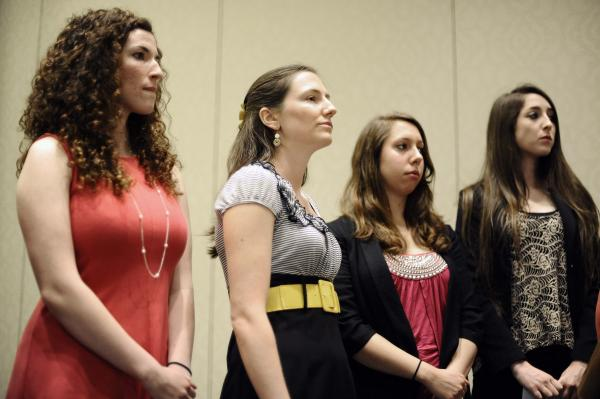 University of Connecticut students Rosemary Richi, left, Kylie Angell, second from left, Erica Daniels, second from right, and Carolyn Luby, right, listen to attorney Gloria Allred speak during a news conference, Friday, July 18, 2014, in Hartford, Conn. The University of Connecticut will pay nearly $1.3 million to settle a federal lawsuit filed by five women who claimed the school responded to their sexual assault complaints with indifference, the two sides announced Friday.