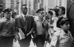 Yusef Salaam walks into court flanked by police and press.
