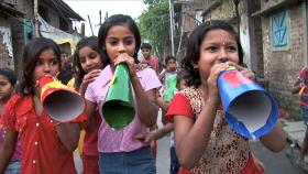 Child activists working with Amlan Ganguly, marching through the streets of Calcutta, using megaphones to spread health messages.