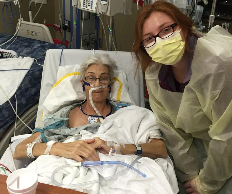 An older woman in a hospital bed, next to a younger woman wearing a mask and gown.