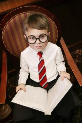 Little boy with glasses, reading a book
