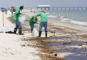 Workers remove oil from the beach at Gulf Shores on June 12, 2010. The Coast Guard and EPA are tightening oversight of waste disposal from the Gulf oil spill.