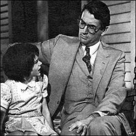 Atticus Finch (played by Gregory Peck) talking with his daughter, Scout (played by Mary Badham).