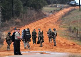 Law enforcement officials outside of the area where Tuesday's school bus shooting suspect is barricaded in a bunker.