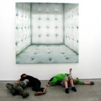 kids wrestling in front of artwork which looks like padded cell