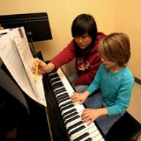 Children at piano with music lesson