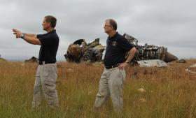 Senior Investigator Joe Sedor (left) shows Member Robert Sumwalt (right) the depth of the debris field of UPS fight 1354.