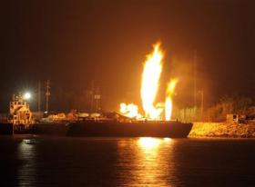 Fire burns aboard two fuel barges along the Mobile River after explosions sent three workers to the hospital Wednesday April 24, 2013.  (AP Photo John David Mercer)