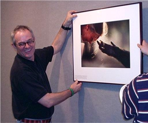 National Geographic photographer Nick Nichols stands with one of his photos.