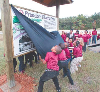 Cobb Elementary students unveil a sign during the groundbreaking of the future Freedom Riders Park.