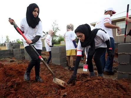 Khawla Alhosani, left, and Zainab Saeed work at a home in the Alberta area of Tuscaloosa Tuesday.